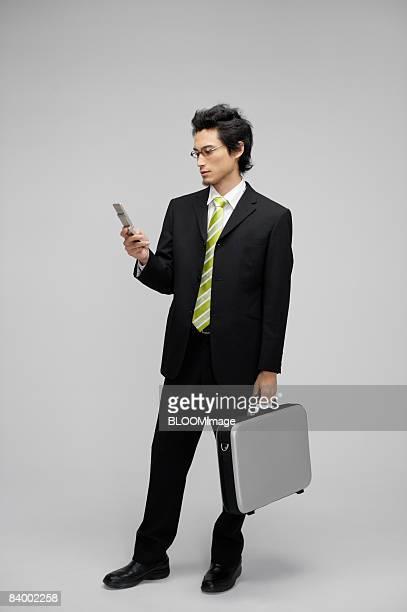 Businessman using cellular phone, holding attache case, studio shot