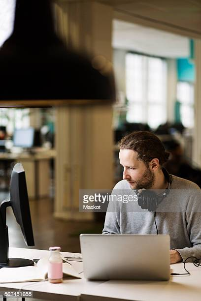 Businessman using computer at desk in creative office