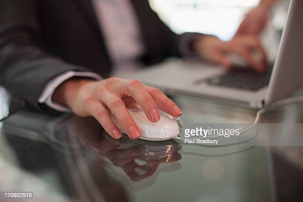 Businessman using computer mouse and typing on laptop