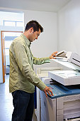 Businessman using copy machine in office