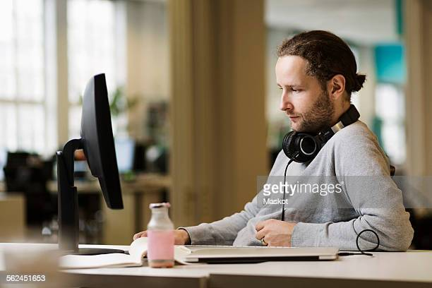 Businessman using desktop PC in creative office