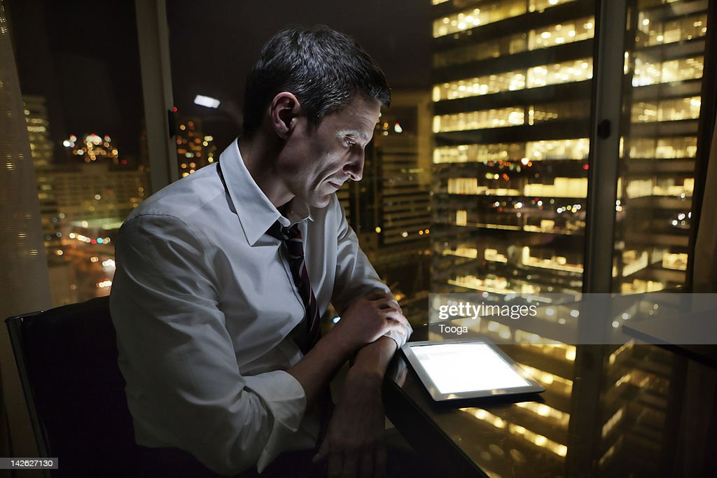 Businessman using digital tablet at night