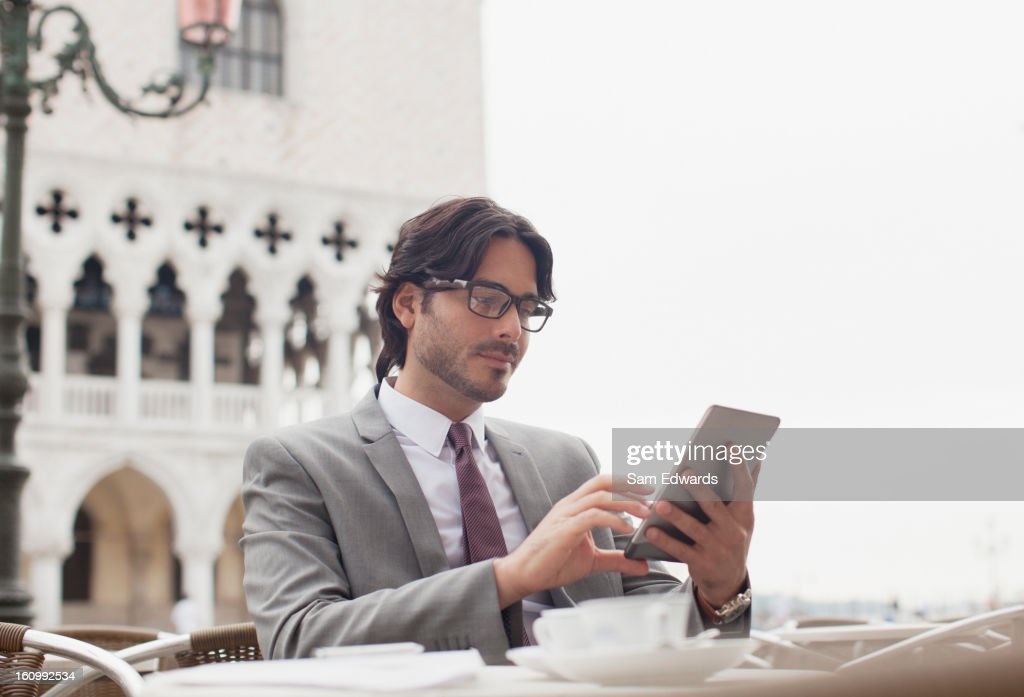 Businessman using digital tablet at sidewalk cafe in Venice : Stock Photo