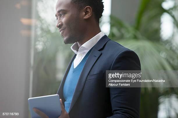Businessman using digital tablet by window