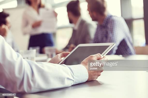 Businessman using digital tablet, close up of hands