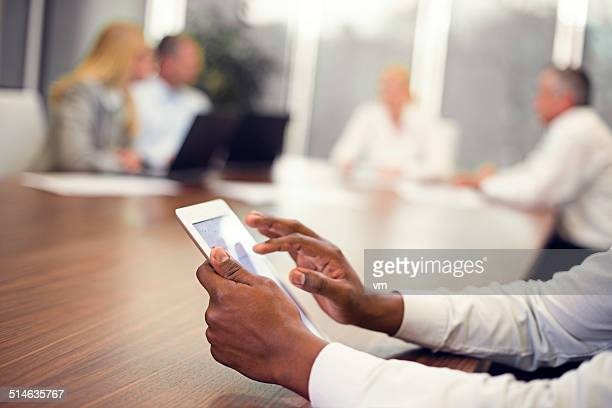 Businessman Using Digital Tablet During Board Meeting