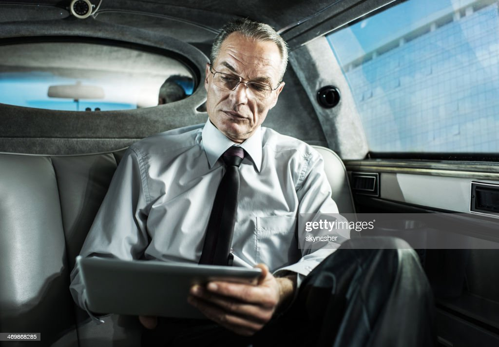 Businessman using digital tablet in a limousine. : Stock Photo