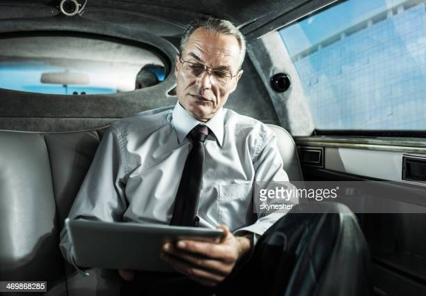 Businessman using digital tablet in a limousine.
