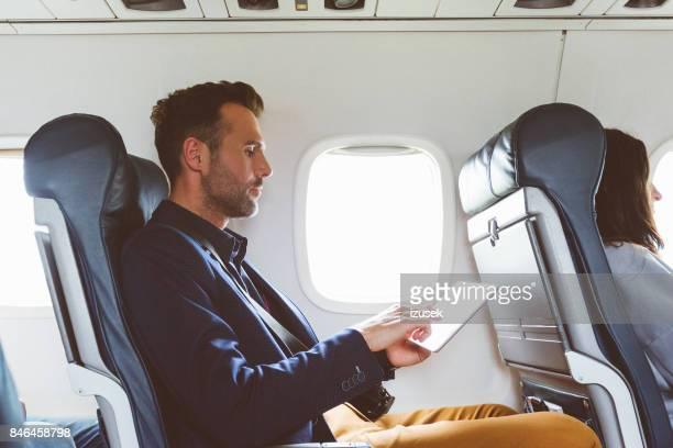 Businessman using digital tablet in airplane