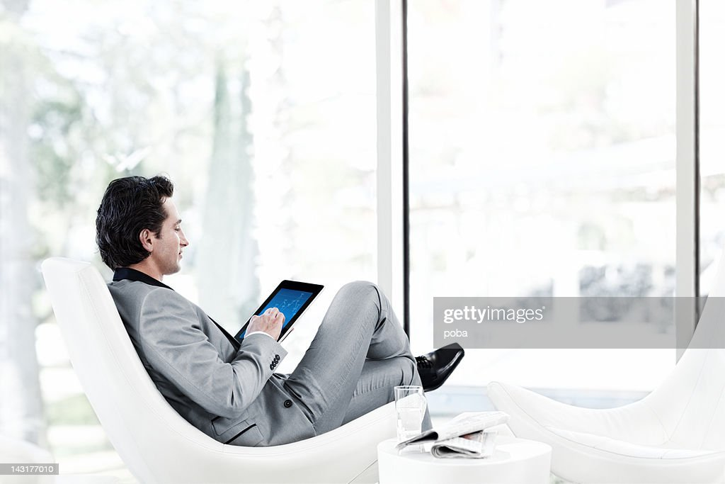 Businessman using digital tablet in armchair : Stock Photo
