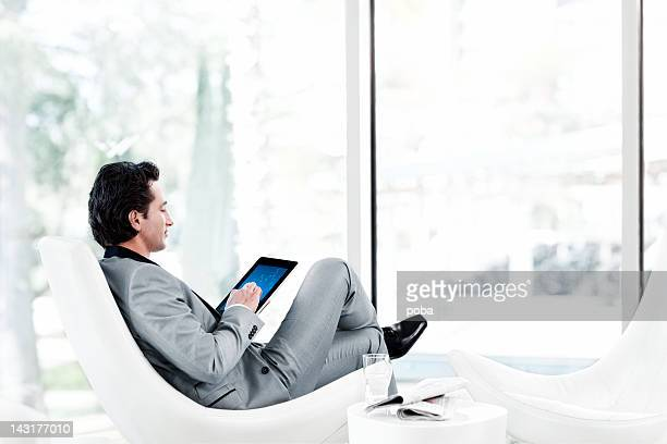 Businessman using digital tablet in armchair