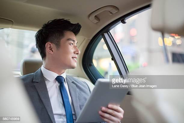 Businessman using digital tablet in car back seat
