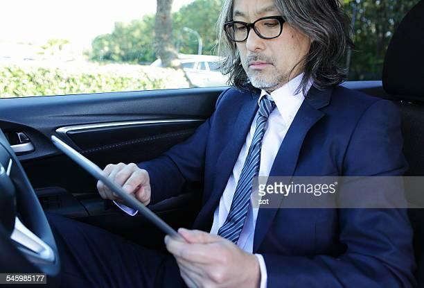 Businessman using digital tablet in car