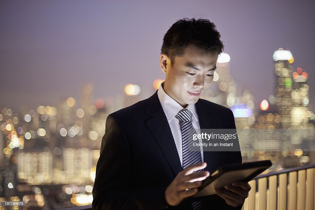 Businessman using digital tablet in city : Stock Photo