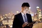 Businessman using digital tablet in city