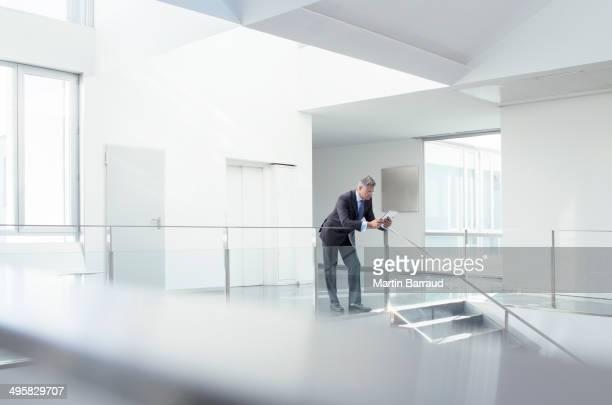 Businessman using digital tablet in corridor
