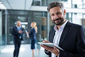 Portrait of businessman using digital tablet in office corridor