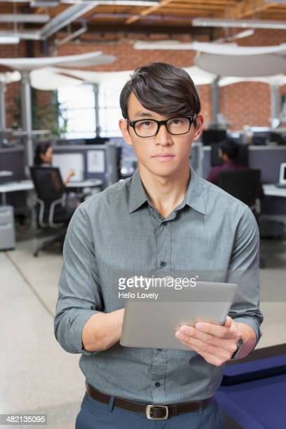Businessman using digital tablet in office lounge area