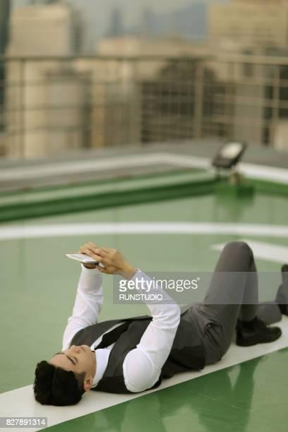 Businessman Using Digital Tablet on a Skyscraper's Rooftop