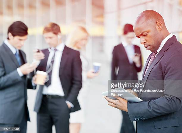 Businessman using digital tablet outdoors