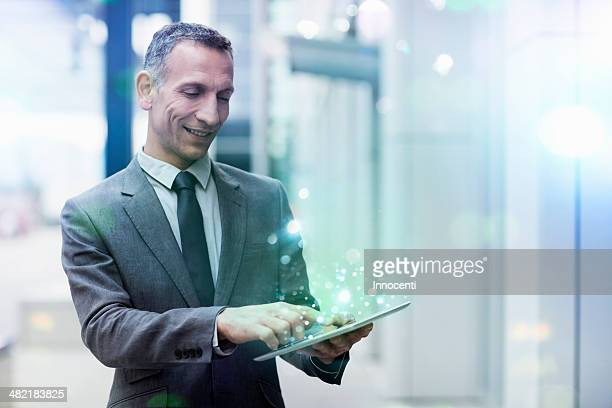 Businessman using digital tablet with glowing lights coming out of it