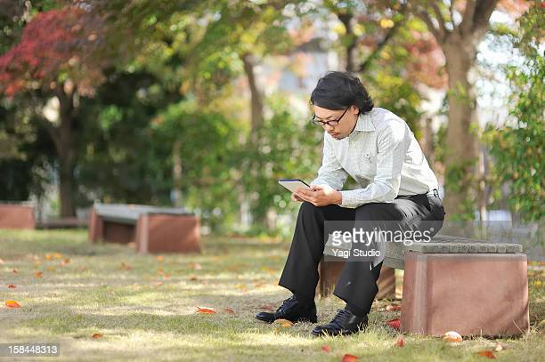 Businessman using digital tablet,Sitting on bench