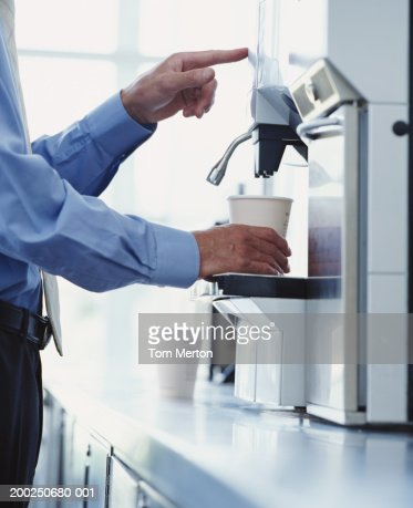 Businessman using drinks machine, close-up : Stock Photo