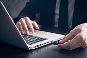 Close up of Businessman using flash drive connect to laptop on the office desk.