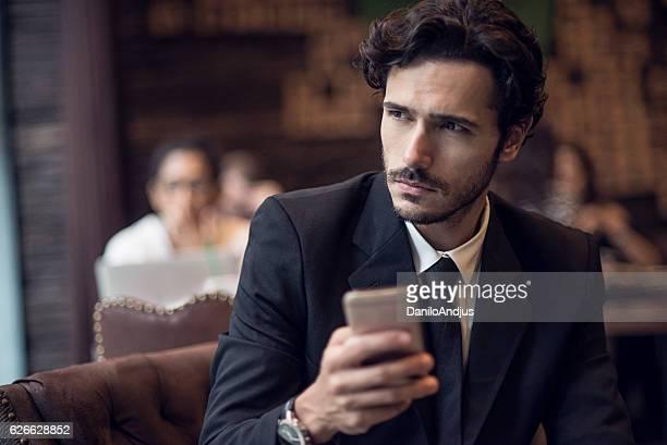 businessman using his smartphone on a coffee break