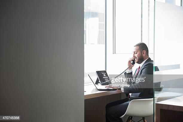 Homme d'affaires à l'aide de téléphone fixe et ordinateur au bureau