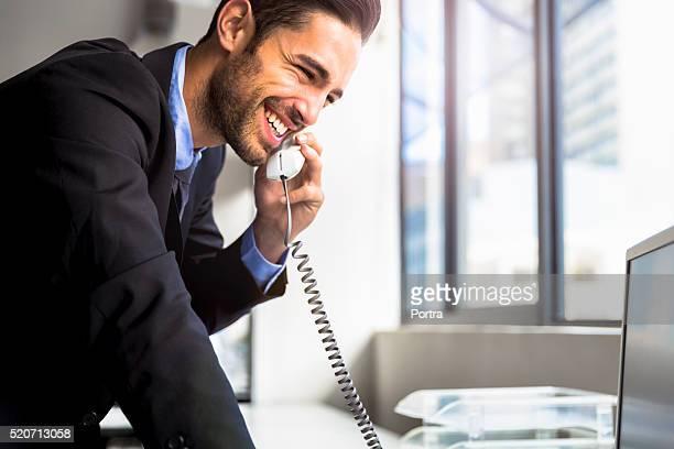 Businessman using landline phone in office