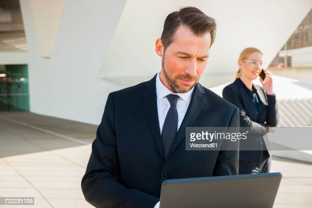 Businessman using laptop and businesswoman on cell phone outdoors