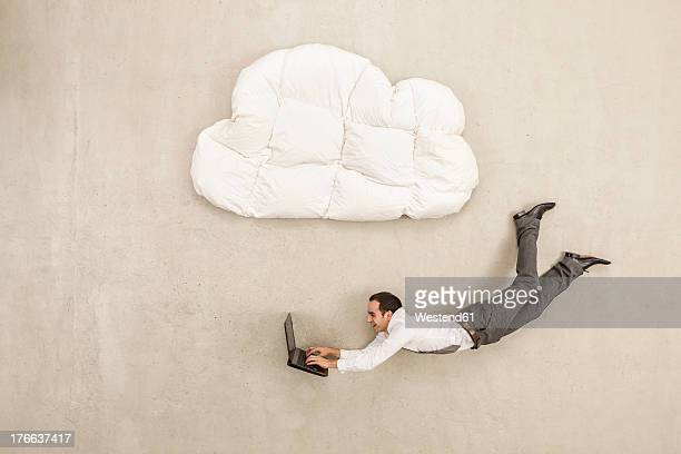 Businessman using laptop and flying below cloud shape pillow