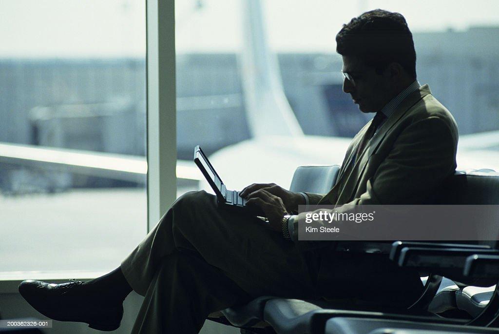 Businessman using laptop at airport : Stock Photo