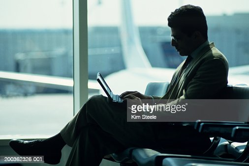 Businessman using laptop at airport : Stock Photo