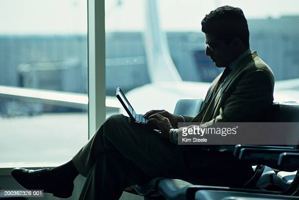 Businessman using laptop at airport