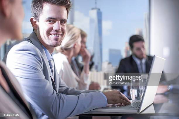 Businessman using laptop at conference table meeting, New York, USA