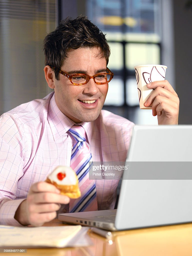 Businessman using laptop at desk, holding cup and cake, smiling : Stock Photo