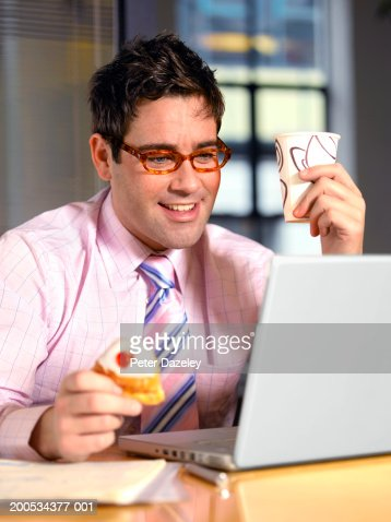 Businessman using laptop at desk, holding cup and cake, smiling : Foto de stock