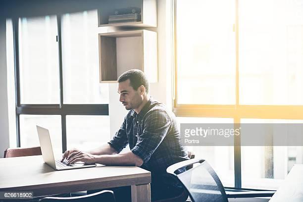 Empresário com o laptop na mesa no escritório