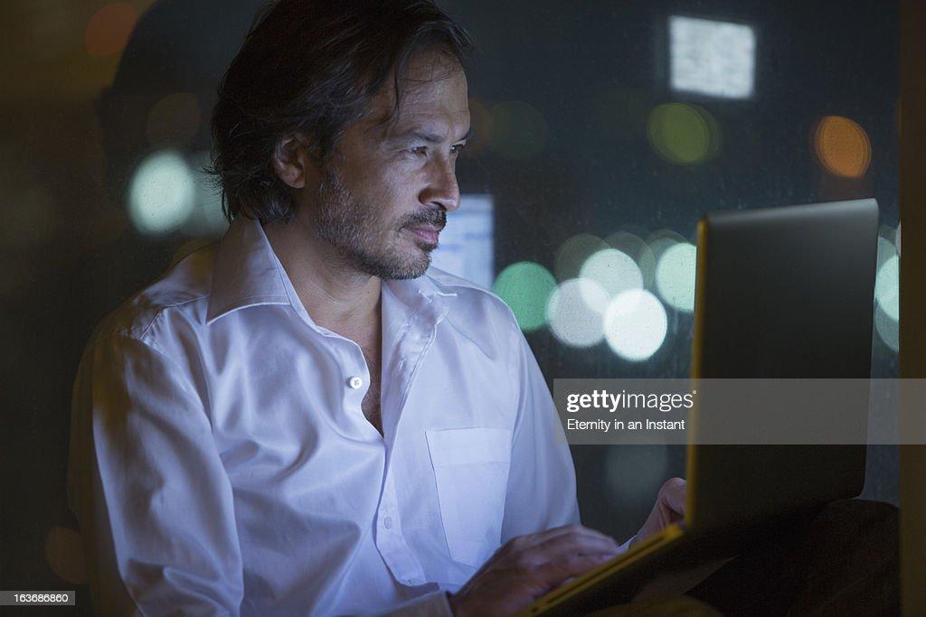 Businessman using laptop computer at night : Stock Photo