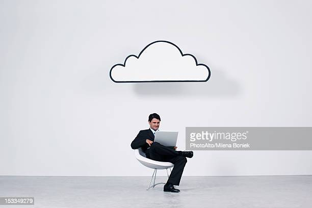 Businessman using laptop computer beneath cloud representing cloud computing