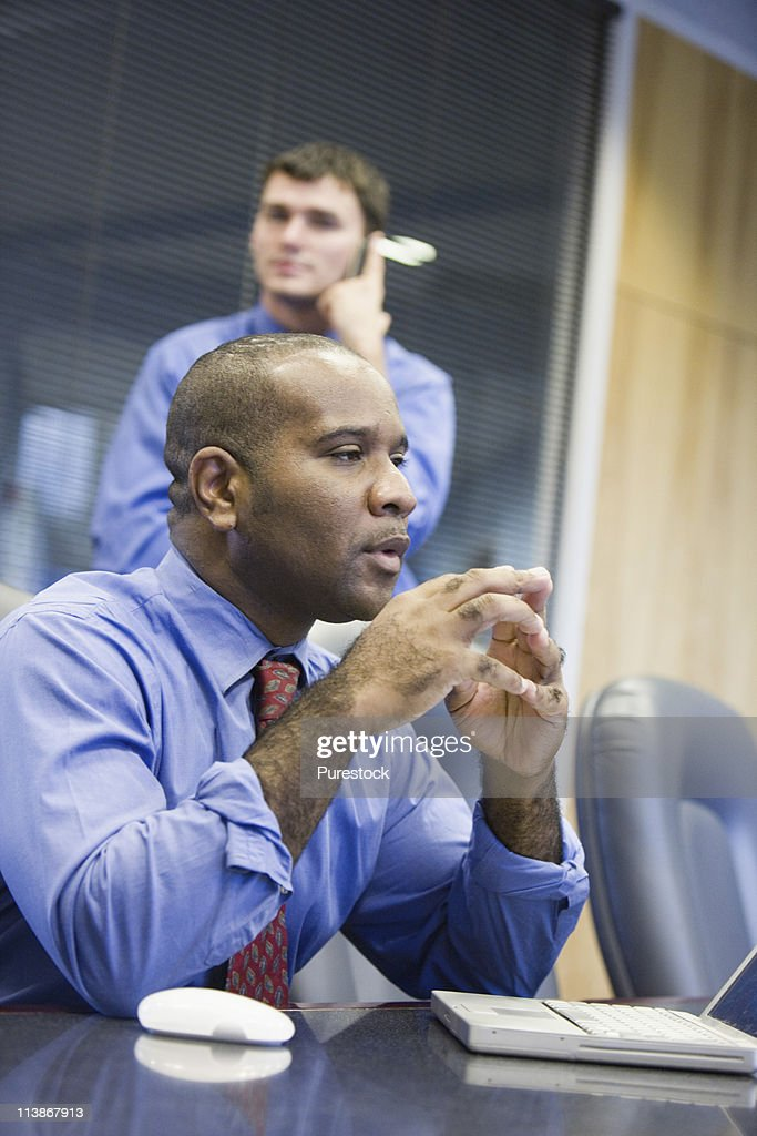 Businessman using laptop computer while colleague uses mobile phone in background : Stock Photo