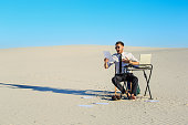 Businessman working and using a laptop in a desert