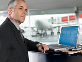 Businessman using laptop in airport, looking into distance, close-up