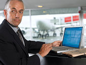 Businessman using laptop in airport, looking over shoulder, close-up