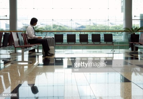 Businessman using laptop in  airport lounge