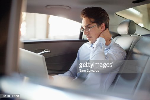 Businessman using laptop in back seat of car : Stock Photo
