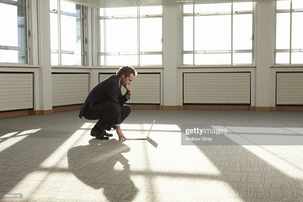 Businessman using laptop in empty office : Stock Photo