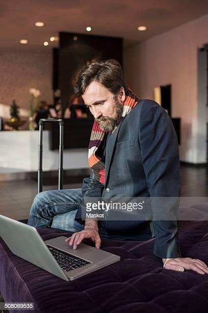 Businessman using laptop in hotel lobby